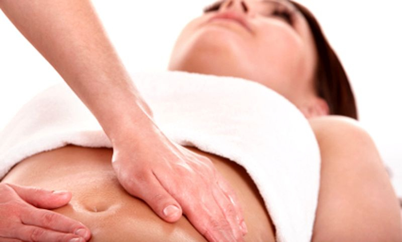 Beautiful young woman having stomach massage.