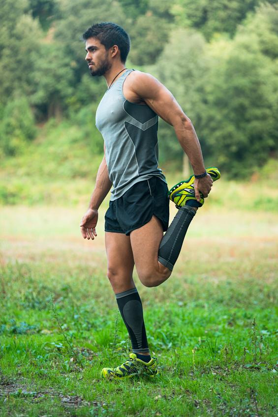 Chico calentando antes de empezar con el deporte en plena natura