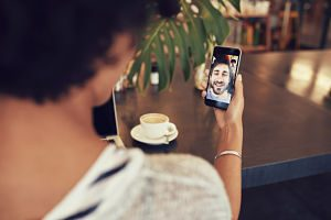 Young an and woman talking to each other through a video call on a smartphone. Young woman having a videochat with man on mobile phone. Woman sitting at a coffee shop.