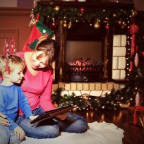 mother and son using tablet pc by a fireplace