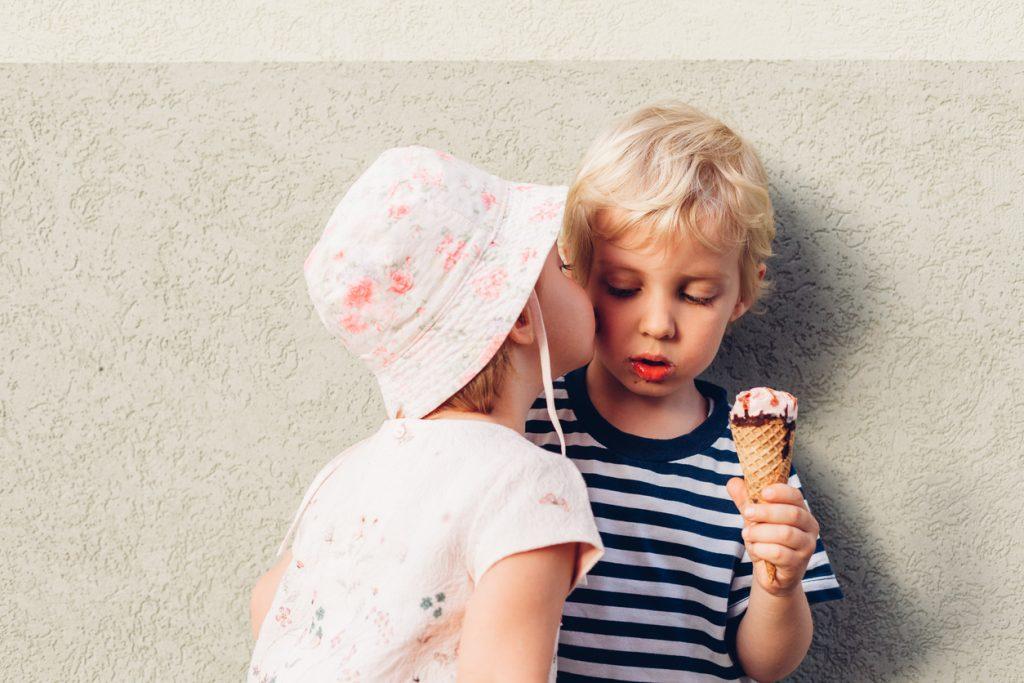 Niña dando un beso a un niño con helado