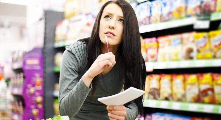 Una-chica-comprueba-la-lista-de-la-compra-en-el-supermercado