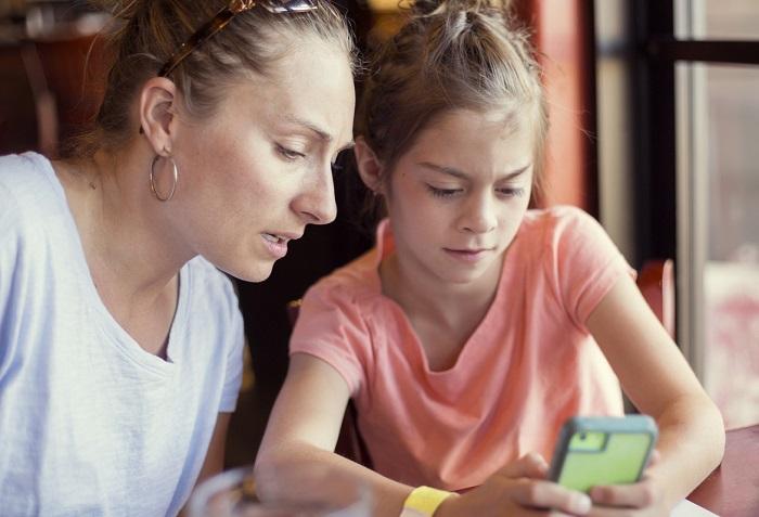 Madre e hija miran un teléfono