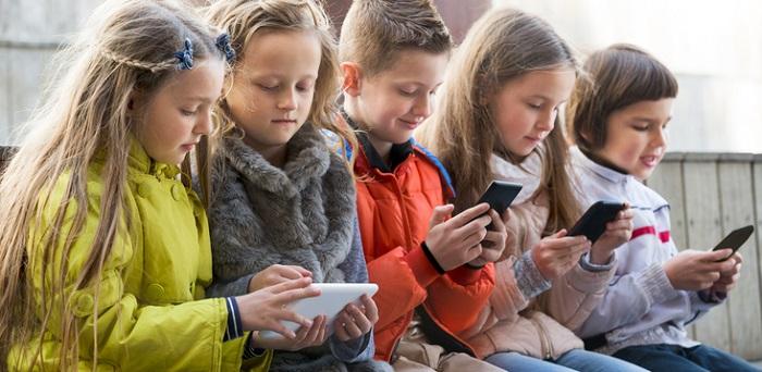 Niños en la calle con móvil