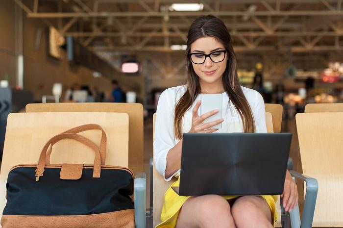 Chica sentada en un aeropuerto con el móvil