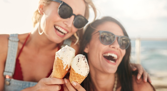 dos amigas sonríen con un helado en la mano