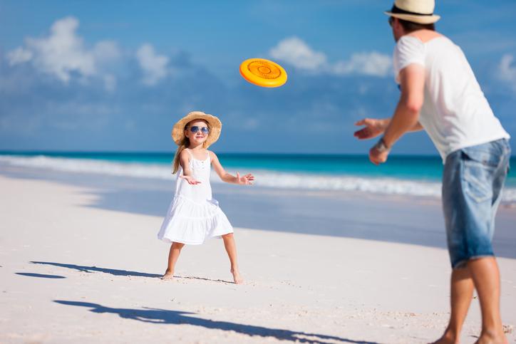 padre e hija juegan en la playa