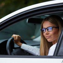 Chica con gafas conduciendo un coche