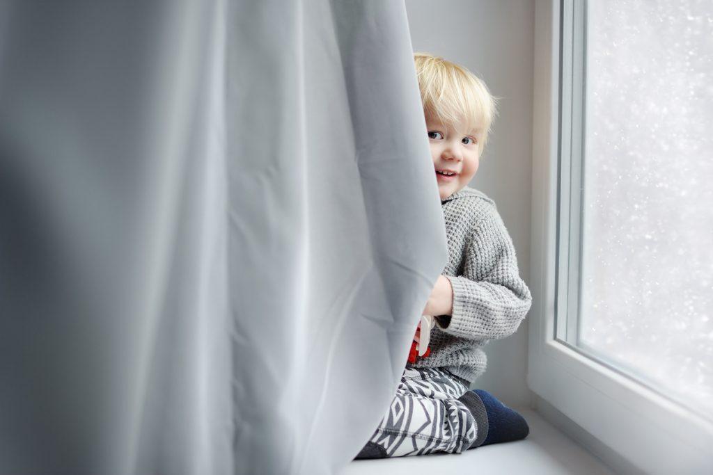 Niño travieso pequeño escondido