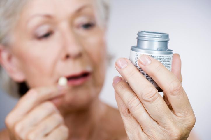 mujer mayor toma pastillas caja