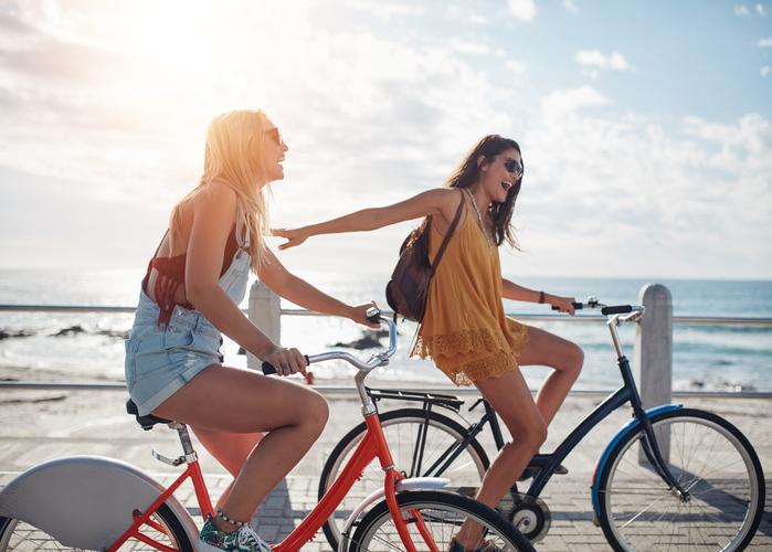 dos amigas en bicicleta en la playa