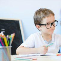 Niño pequeño estudiando en el cole