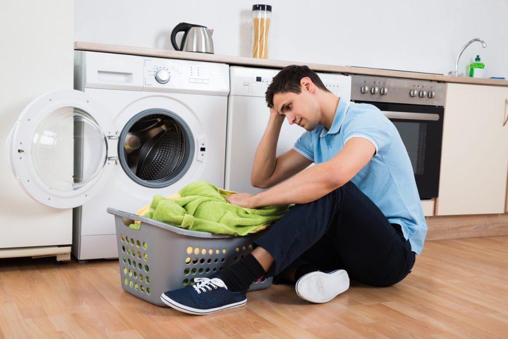 Joven prepara lavadora rebuscando en la cesta