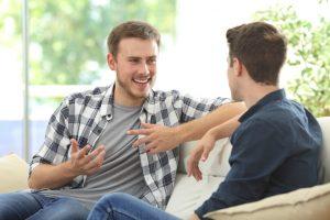 dos amigos hablan y sonríen sentados en un sofá