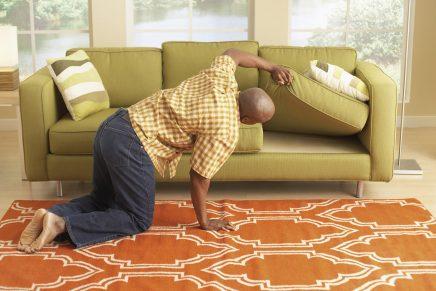 hombre busca en su sofá el mando de la televisión