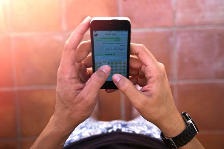 Una persona mantiene una conversación por WhatsApp con emoticonos