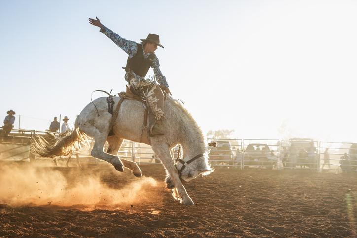 un cowboy haciendo un rodeo con un caballo
