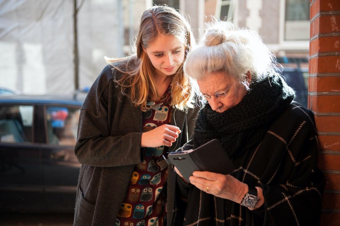 Una señora mira el teléfono con la supervisión de una joven