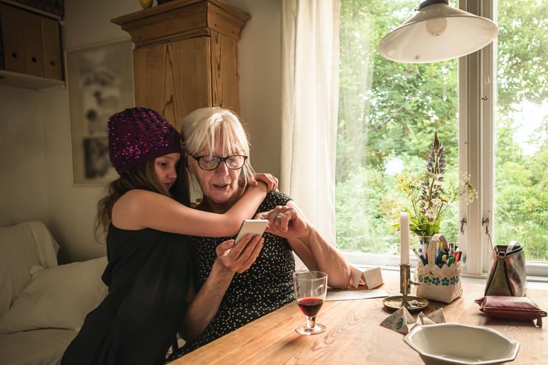 Una abuela trastea con el móvil junto a su nieta