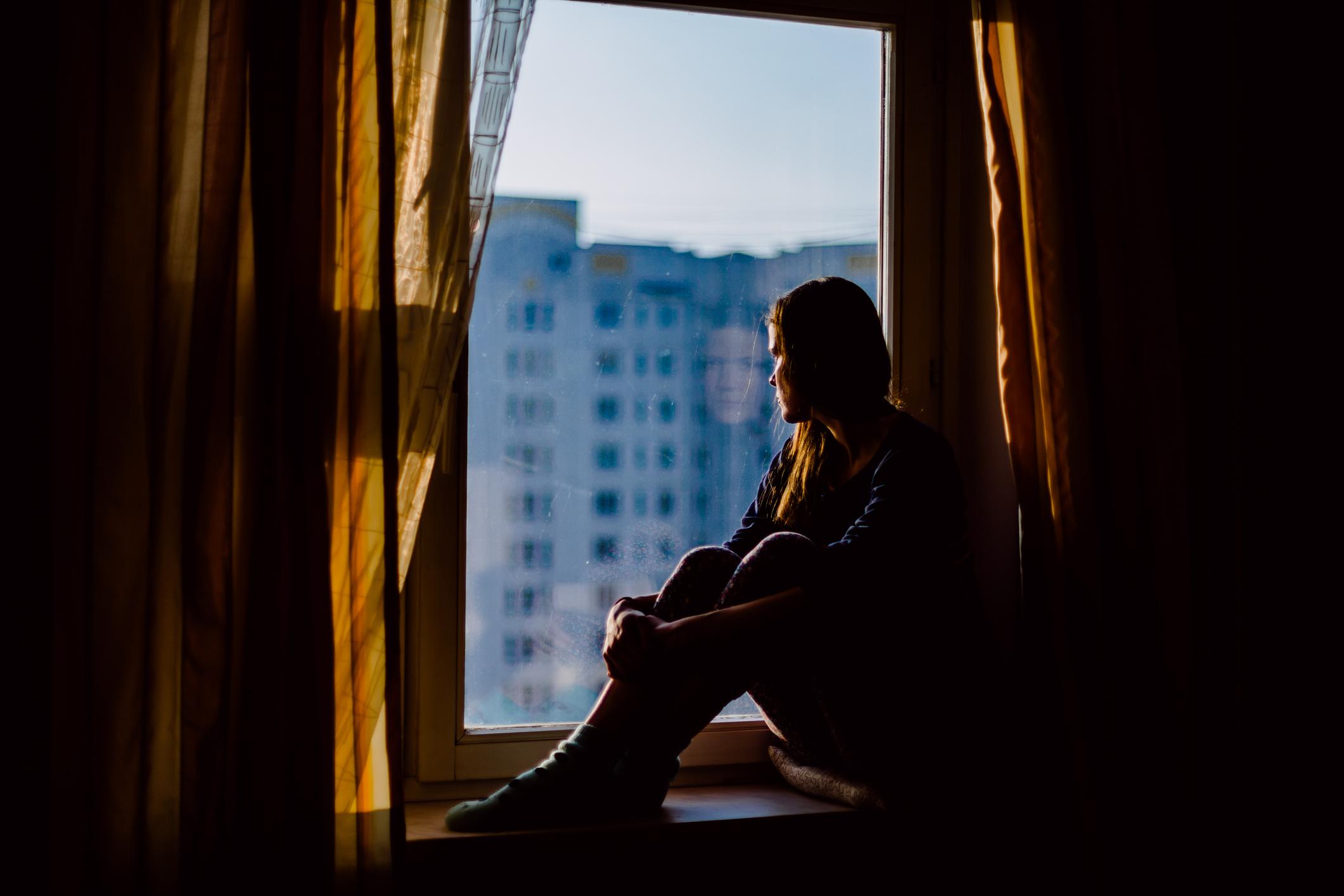 Mujer mira por la ventana