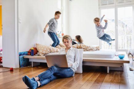 Madre teletrabajando con sus hijos en casa