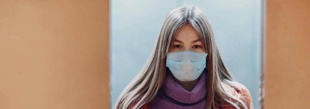 Mujer con mascarilla en un ascensor