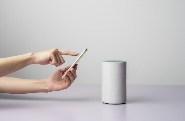 Teléfono móvil junto a un altavoz inteligente