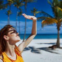 Joven en la playa deslumbrada por el sol