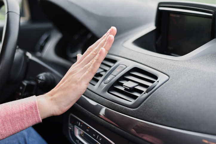 Cropped Hand Of Woman Over Air Conditioner In Car