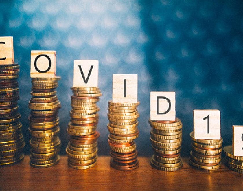 Diminishing stacks of coins with COVID-19 (Coronavirus disease) written on them