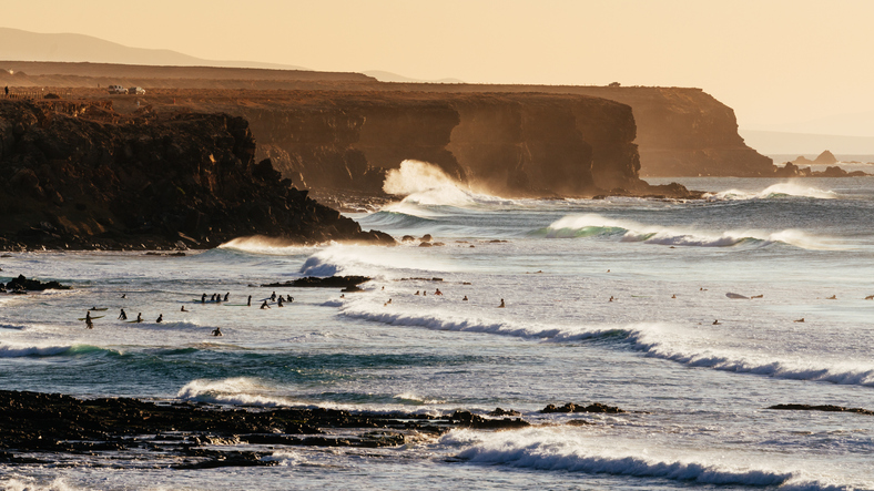 El Cotillo cliffs and beaches with waves and surfers at sunset, Fuerteventura