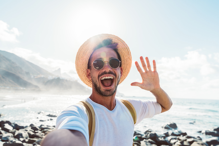 Portrait Of Man With Mouth Open Waving While Standing At Beach