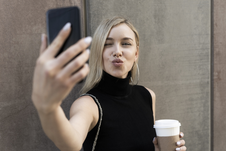 Portrait of blond woman with coffee to go taking selfie with smartphone